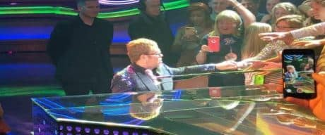 Elton John in concert on piano.