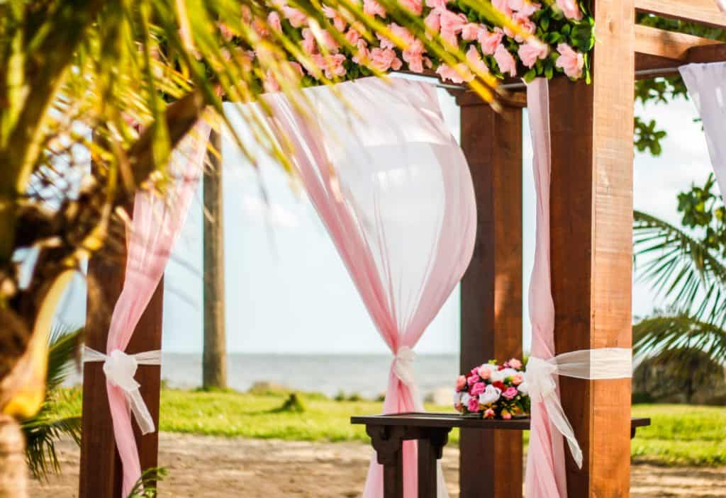 Wedding venue gazebo decorated with pink ribbons.