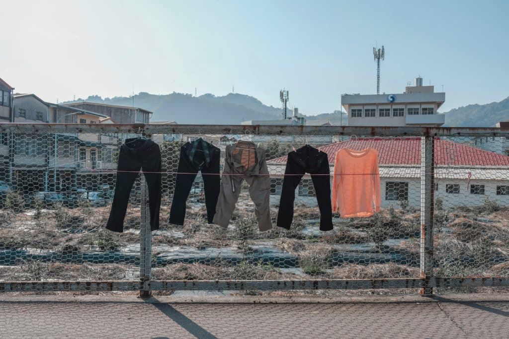 Things we waste money on clothing pic. Pants and tops hanging on a wire fence.