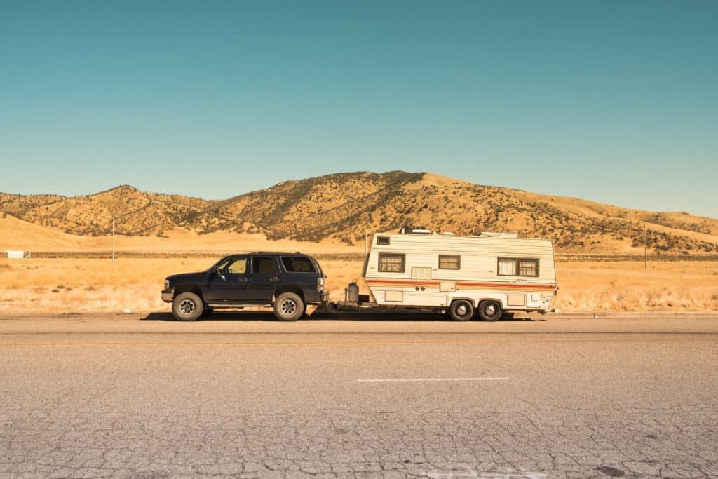 Black car towing a camper - why working from the road will change your life